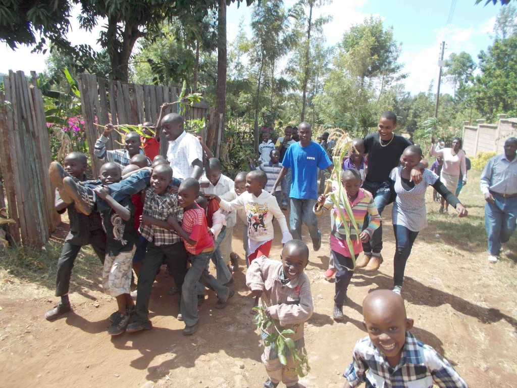 Moses Maingi and Kelvin Mutuma Naari being carried up Tungi Hill to Hope Children's Home after learning of their successful results on the exam that will determine their academic futures.