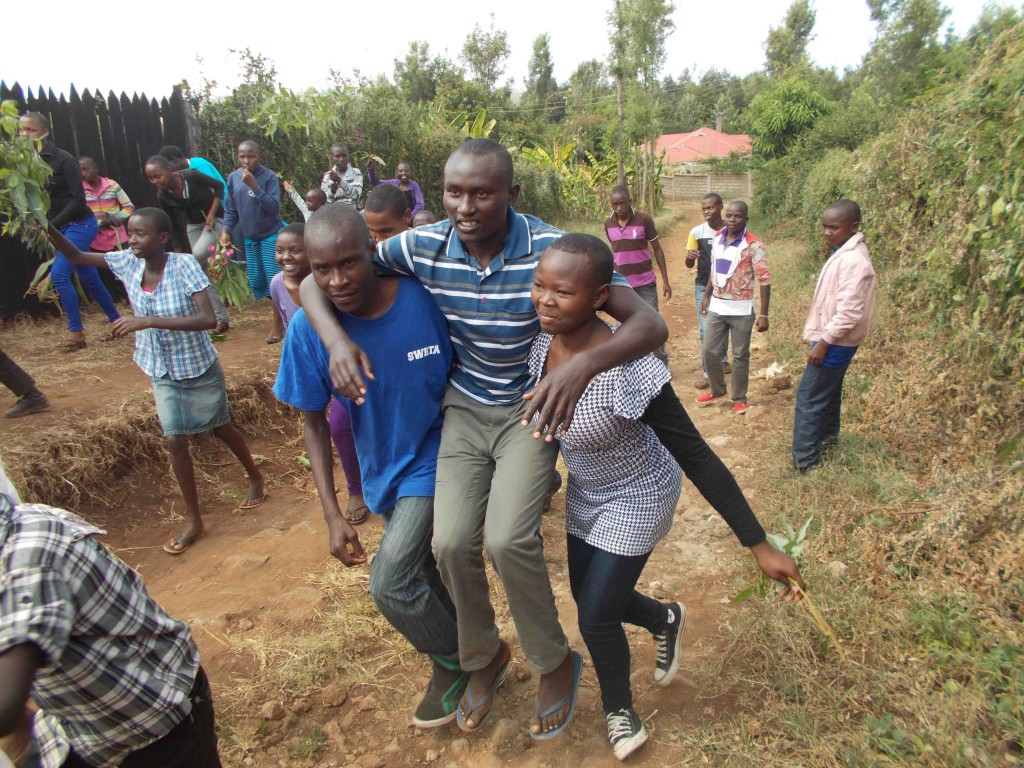 Recent Secondary School graduate Ken Muthuyia is carried up Tungi Hill for a celebration of his achievement on graduating from Secondary School.