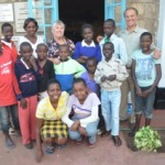 Ed and Yvette, with a staff member and some of our younger children, in front of the dining hall at the Home.